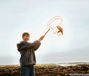 A young pre-teen boy is proudly holding up a starfish he caught in his fishing net.  The boy is wearing a sweatshirt and jeans.  A boy catching a starfish at the tidal pools at low tide near the ocean.